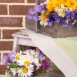 Beautiful flowers in crates on small ladder on brick wall background — Stock Photo #48370875