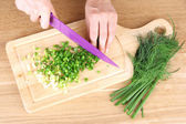 Female hand cutting chives on cutting board — Stockfoto