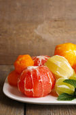 Citrus fruits without skin, on plate, on wooden background — Stock Photo