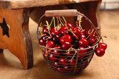 Fresh cherries in basket on wooden background — Stock Photo