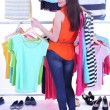 Young woman choose clothes near rack with hangers — Stock Photo #48398401