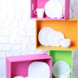 Beautiful  bright shelves and boxes with tableware  on  light wall background — Stock Photo #48398821