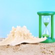 Hourglass in sand on blue sky background — Stock Photo #48399649