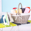 Basket with laundry and ironing board on home interior background — Stock Photo