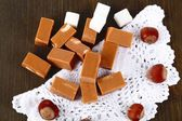 Many toffee on napkin on wooden table — Stock Photo