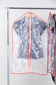 Office female clothes in cases for storing on hangers, on gray background — Stockfoto