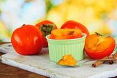 Ripe persimmons with cinnamon on table on bright background — Stock Photo