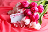 Beautiful tulips on color  fabric background — Stok fotoğraf