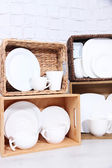 Beautiful shelves and boxes with tableware  on  light wall background — Stock Photo