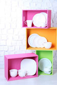 Beautiful  bright shelves and boxes with tableware  on  light wall background — Stok fotoğraf