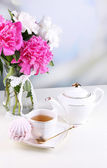 Composition of beautiful peonies in vase, tea in cup and marshmallow, on table, on light background — Stock Photo
