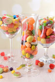 Different colorful fruit candy in glasses on table on light background — Stock Photo