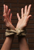Tied hands on dark background — Stock Photo