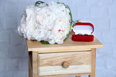 Beautiful wedding bouquet on   wooden stand on light wall background — Stock Photo