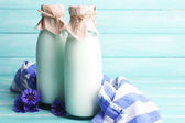 Bottles of milk and cornflowers on wooden table — Stock Photo