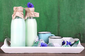 Bottles and cups of milk with cornflowers on wooden tray — Stock Photo