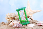 Hourglass in sand on bright background — Stock Photo