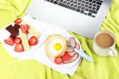 Composition with laptop and tasty breakfast on wooden tray, close-up — Stock Photo