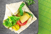 Veggie wrap filled with chicken and fresh vegetables on table — Stock Photo