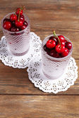 Sweet cherries in glasses on wooden table — Stock Photo