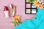 Eyeshadow, lipstick and flowers on color wooden background — Stock Photo