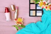 眼影、 唇膏和色木背景上的花朵 — 图库照片