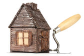Wooden toy house on trowel and tiles, isolated on white — Stock Photo
