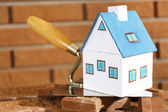 Wooden toy house on trowel and tiles on brick wall background  — Stock Photo