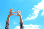 Young girl holding hands in heart shape framing on blue sky background — Stock Photo