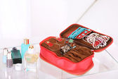 Handbag with accessorises and perfumes in bottles on table on  home interior background — Foto de Stock