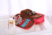 Handbag with accessorises and perfumes in bottles on table on  home interior background — Stock Photo