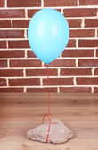 Color balloon with stone on brick wall background — Stock Photo