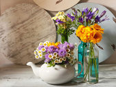 Kitchen decoration with teapot and wild flowers on wooden background — Stock Photo