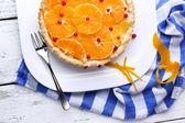 Homemade orange tart on plate, on color wooden background — Stock Photo
