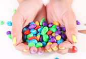 Female hands with stylish colorful nails holding multicolor candies, isolated on white — Foto de Stock