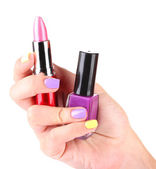 Female hands with stylish colorful nails holding lipstick and nail polish bottle, isolated on white — Stock Photo