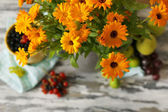 Flowers and fruits on wooden table — Stock Photo