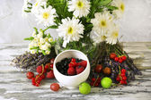 Still life with flowers and fruits on table — Stock Photo