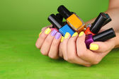 Female hands with stylish colorful nails holding bottles with nail polish, on green background — Stock Photo