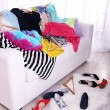 Messy colorful clothing on  sofa on light background — Stock Photo #48448419