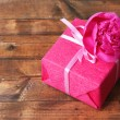 Pink gift with bow and flower on wooden table close-up — Stock Photo #48448785