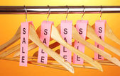 Wooden clothes hangers as sale symbol on orange backgroun — Stok fotoğraf