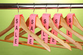 Wooden clothes hangers as sale symbol on green backgroun — Stok fotoğraf