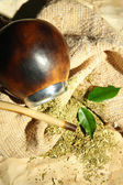 Calabash and bombilla with yerba mate on burlap background — ストック写真