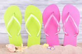 Bright flip-flops on sand, on wooden background — Stock Photo