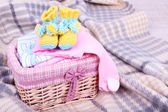 Baby clothes in basket on plaid in room — Stock Photo