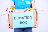 Volunteer with donation box with foodstuffs on grey background — Stock Photo