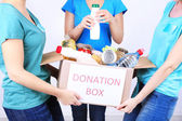 Volunteers with donation box with foodstuffs on grey background — Stock Photo