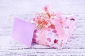 Regalo rosa con fiocco e fiore sul primo piano tavolo in legno — Foto Stock