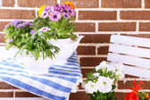 Flowers in  decorative pots on table, on bricks background — Stok fotoğraf